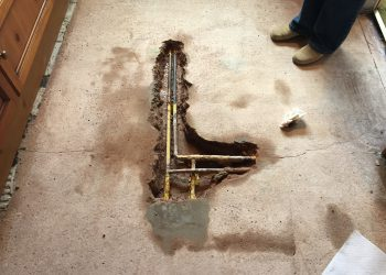 hole in floor revealing pipes